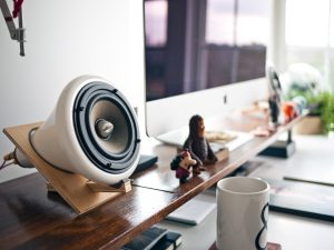desk setup with large speaker and coffee mug, stock image for the article 5 Overused Marketing Buzzwords