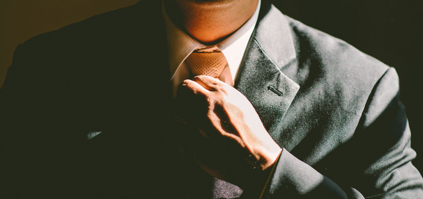 Man in suit tightening his tie. Why you should network more. future access. Niagara