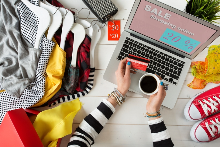 flat lay image of woman shopping online with clothing next to laptop. how to ramp up your business for the holiday season with Future Access. St. Catharines. Developing a marketing strategy for the holidays.