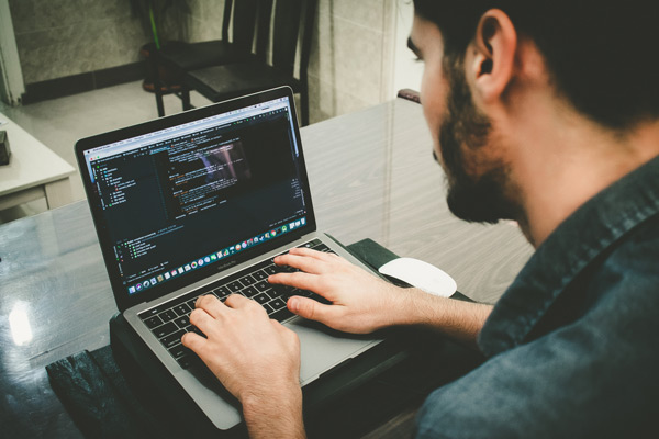 man coding on laptop in an office